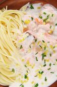 fresh rose wild salmon baked in cream cheese sauce with italian pasta on wooden plate isolated over