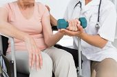 Female physiotherapist assisting senior woman to lift dumbbell in the medical office