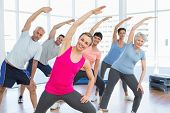 stock photo of pilates  - Happy female trainer with class stretching hands at yoga class - JPG