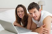 Smiling young couple using laptop in bed at home