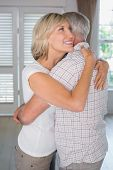 Side view of a mature couple embracing at home
