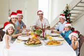 Portrait of happy multigeneration family in Santa hats having Christmas meal at dining table