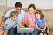 Family of four using laptop together while sitting on sofa at home