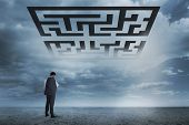Businessman standing against maze in sky above desert landscape