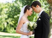 Side view of young newly wed couple with head to head standing in garden