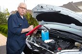 Auto mechanic checking engine. Car repair service.