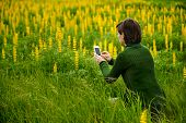 Woman taking pictures to flowers with a cellphone