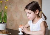 Preschooler girl with Easter egg for breakfast