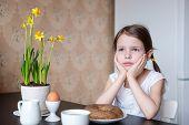 Nice thoughtful  preschooler girl with breakfast