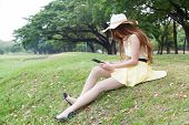 Woman Sitting On Grass And Using A Tablet.