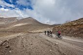 KARDUNG LA PASS, INDIA - SEPTEMBER 5, 2011: Bicycle tourists in Himalayas ascend Khardung La - highe