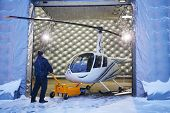 MOSCOW, RUSSIA - DEC 21, 2013: Man rolls out new private helicopter from hangar of Heliport Moscow - unique project to create Europe largest helicopter multi-center for more than 200 aircraft.