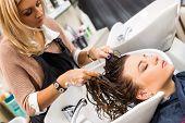 Hairdresser salon. Woman during hair wash
