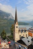 Slender belfry, Lutheran church on the shore of Lake Hallstatt. Opposite shore of the lake - the bea