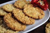 Traditional Anzac Biscuits On Dark Recycled Wood With Remembrance Red Poppy For Anzac Day Or Remembr