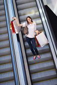 Happy young woman on scalators in a shopping mall with colorful fashion gift  bags