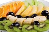 Fresh fruits sliced on white plate