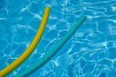 Yellow And Blue Noodles In Swimming-pool. Blue Water.