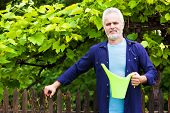 Portrait Of Senior Man With Watering Can In Garden