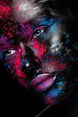 Portrait of beautiful girl with bright fashion art makeup with black face . Over black background