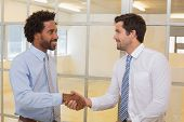 Two smiling young businessmen shaking hands in the office