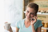 Smiling young woman drinking coffee while using mobile phone in the coffee shop