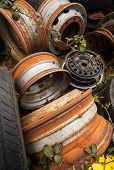 image of big-rig  - rusting car and big rig wheels in a scrapyard - JPG