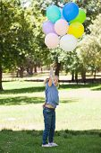 Full length of a young girl with colorful balloons standing at the park