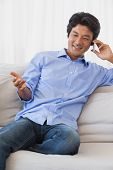 Happy man sitting on couch on the phone at home in the living room