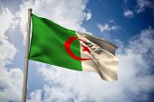 Algeria national flag against bright blue sky with clouds