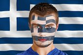 Composite image of serious young greece fan with facepaint against digitally generated greek national flag