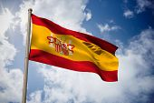 Spain national flag against bright blue sky with clouds