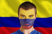 Composite image of serious young colombia fan with facepaint against digitally generated colombia national flag