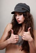 Trendy Happy Girl In Cap Showing Thumb Up Sign