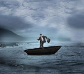 Composite image of happy businessman in a sailboat on open water