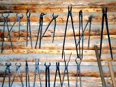 pic of blacksmith shop  - Blacksmith tools displayed on a wall indoors - JPG