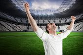 Excited football fan cheering in a vast football stadium with fans in white
