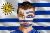 Composite image of serious young uruguay fan with facepaint against digitally generated uruguay nati