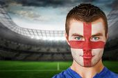 Composite image of serious young england fan with face paint against large football stadium with lig
