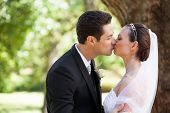 Side view of a romantic newlywed couple kissing in the park