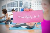 Fit blonde holding card saying mind body soul against yoga class in gym