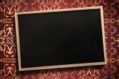 Chalkboard with wooden frame against elegant patterned wallpaper in red and gold