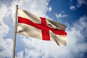 England national flag against bright blue sky with clouds