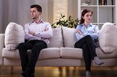 stock photo of sorrow  - Young couple sitting on the sofa after quarrel - JPG