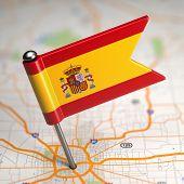 Spain Small Flag on a Map Background.
