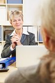 Friendly bank adviser listening to senior woman in her office