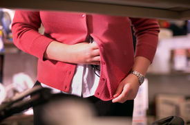picture of shoplifting  - A female in the act of shoplifting or stealing puts an item under her clothes - JPG