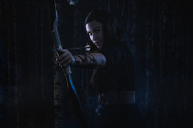 foto of fletching  - Beautiful archery woman aiming gloomy atmosphere forest on background - JPG