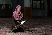 stock photo of islamic religious holy book  - Muslim Woman Reading Holy Islamic Book Koran - JPG