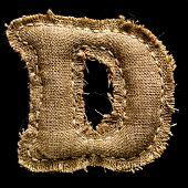 Linen or hemp vintage cloth letter D isolated on black background